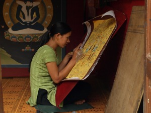Woman making a prayer wheel.