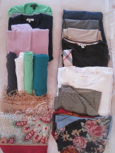 In the checked bag: one sweater, one cozy, one cardigan, five t-shirts, two lightweight long-sleeve shirts, two fancy shirts, one pair of cords, one pair of khaki's, one pair of trouser jeans. Not pictured: three pairs of shoes: one pair of ballet flats, one pair of loafers and one pair of wedges.